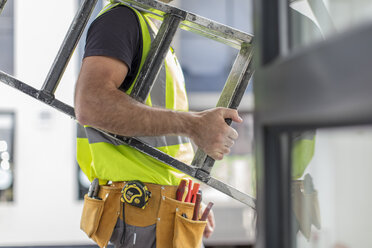Close-up of construction worker carrying ladder - ZEF15353