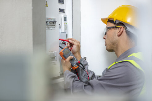 Electrician working with voltmeter at fusebox - ZEF15356
