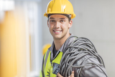 Portrait of smiling electrician with cable on construction site - ZEF15365