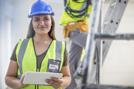 Portrait of smiling woman with tablet on construction site - ZEF15368