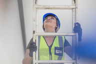 Young woman on construction site climbing ladder - ZEF15371