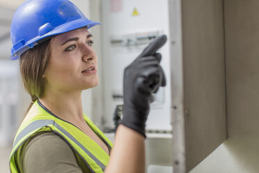 Young female electrician working at fusebox - ZEF15374