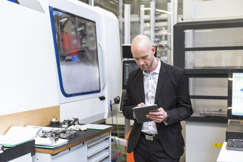 Businessman using tablet in modern factory - DIGF03815
