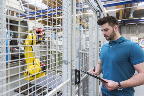 Man with clipboard standing at industrial robot in modern factory - DIGF03833