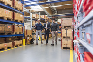 Three men walking and talking in factory storeroom - DIGF03848