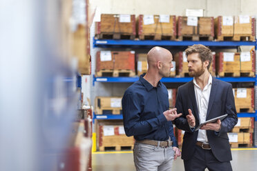 Two businessmen with tablet talking in factory storeroom - DIGF03851