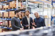 Three men talking in factory storeroom - DIGF03857