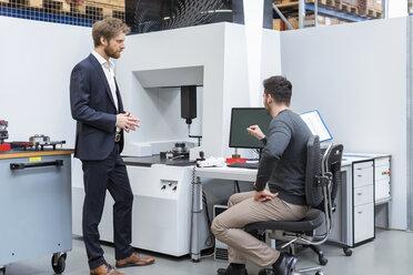 Two men talking at machine in modern factory - DIGF03860