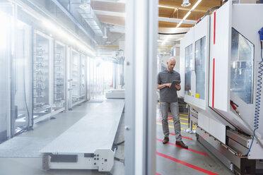 Man using tablet in modern factory - DIGF03872