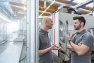 Two men discussing at machine in modern factory - DIGF03875
