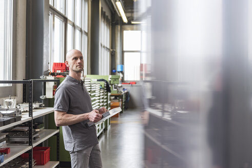 Man standing in modern factory holding product - DIGF03878