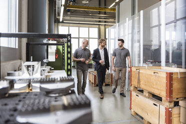 Three men walking and talking in factory - DIGF03881