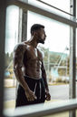 Tattooed physical athlete standing on sports field - DAWF00594