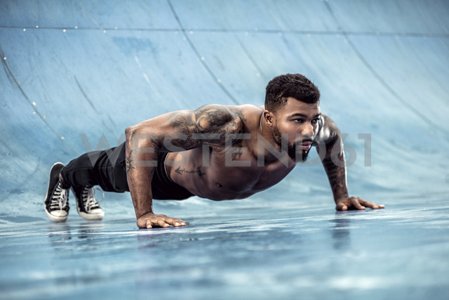 Tattooed physical athlete doing pushups on sports field - DAWF00603 - Daniel Waschnig Photography/Westend61