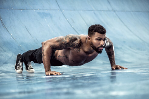 Tattooed physical athlete doing pushups on sports field - DAWF00603