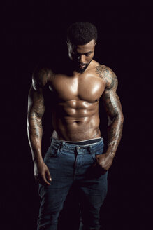 Tattooed physical athlete in front of black background - DAWF00606