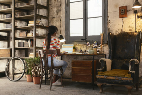 Back view of young woman sitting at desk in a loft working on laptop - EBSF02283