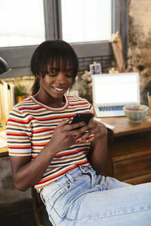 Portrait of smiling young woman sitting in front of desk in a loft using cell phone - EBSF02286
