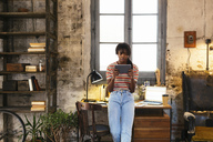 Young woman standing in front of desk in a loft using tablet - EBSF02292