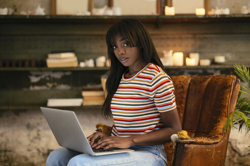 Portrait of young woman sitting on an old leather chair working on laptop in a loft - EBSF02298