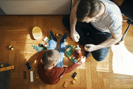 Father and son sitting on the floor playing together with building bricks, top view - ZEDF01275