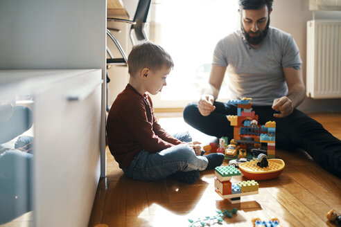 Father playing with building bricks on the floor at home ignoring his sad little son sitting beside him - ZEDF01278