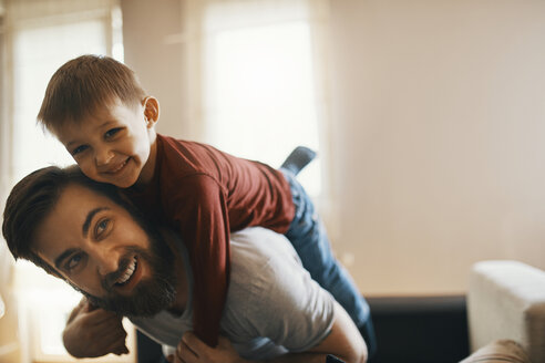 Portrait of happy father and little son playing together at home - ZEDF01290