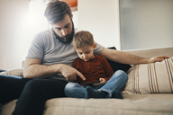 Father and little son sitting together on the couch looking at smartphone - ZEDF01293