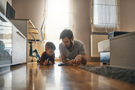 Father and son lying together on the floor playing with toy cars - ZEDF01296
