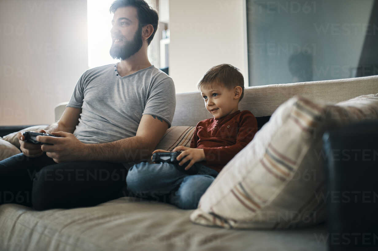 Father and son sitting together on the couch playing computer game - ZEDF01299 - Zeljko Dangubic/Westend61