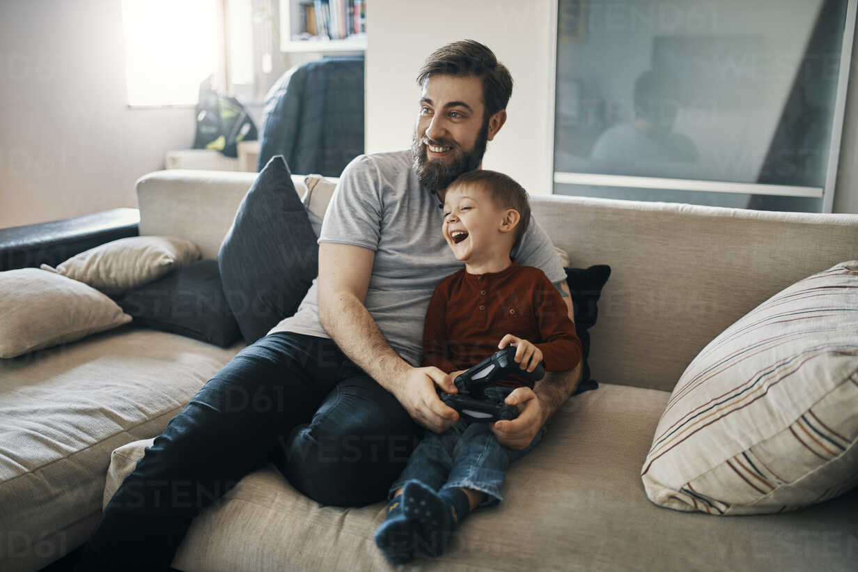 Happy father and son sitting together on the couch playing computer game - ZEDF01302 - Zeljko Dangubic/Westend61
