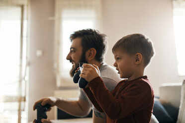 Little boy playing computer game with his father at home - ZEDF01305