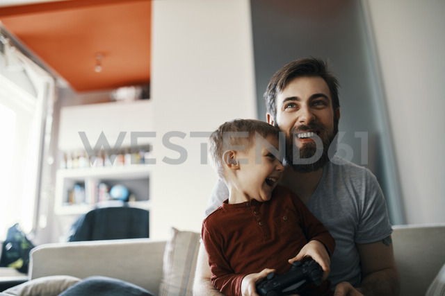 Father and son sitting together on the couch playing computer game - ZEDF01308 - Zeljko Dangubic/Westend61