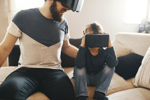 Father and little son wearing virtual reality glasses at home - ZEDF01326