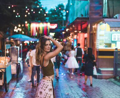 Thailand, Bangkok, young woman in the city on the street at night - AFVF00385