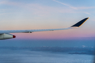 Wing of a plane above the clouds with mountains in background - AFVF00394