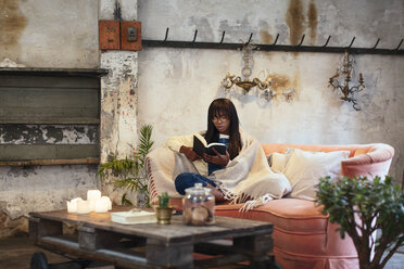 Young woman sitting on the couch at home reading book - EBSF02320