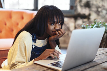 Portrait of smiling young woman using laptop at home - EBSF02332