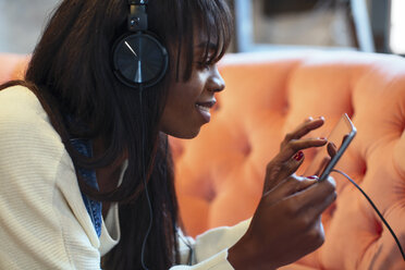 Smiling young woman on the couch using tablet and headphones - EBSF02335