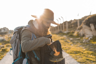 Italy, Sardinia, bearded hiker with hat and backpack at backlight - AFVF00403