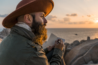 Italy, Sardinia, bearded man with notebook in front of the sea at sunset - AFVF00412