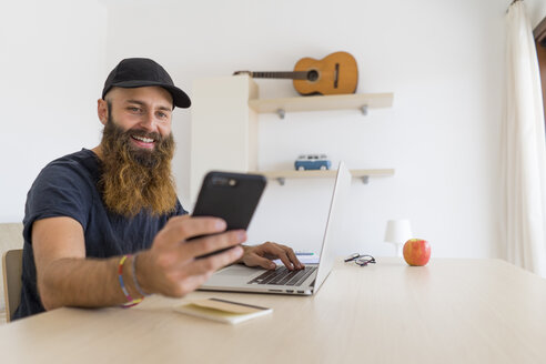 Portrait of bearded young man sitting at desk with laptop looking at cell phone - AFVF00424