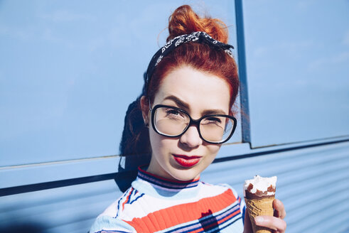 Portrait of redhead young woman holding ice cream cone against mini van - MASF01361
