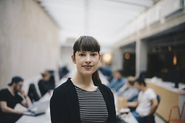 Portrait of female confident computer programmer at office with colleagues working in background - MASF01373