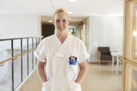 Portrait of happy female nurse standing with hands in pockets at hospital corridor - MASF01376
