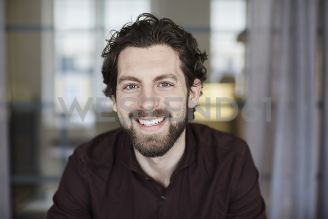 Portrait of smiling businessman standing at creative office - MASF01382