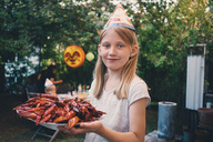 Portrait of girl holding plate with cooked crayfish at garden dinner party - MASF01391