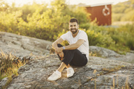 Portrait of smiling man sitting on rock formation during sunny day - MASF01403