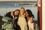Portrait of smiling young female friends standing with arms around at harbor against sky - MASF01406