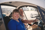 Portrait of smiling senior woman and man enjoying car ride on sunny day - MASF01415